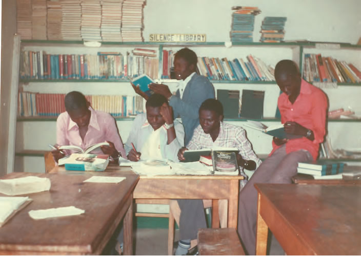 "At the library in Onjiko Secondary School, swotting for the Kenyan Secondary Education (""O"" Level) exams, November 1982. From left to right: The Candidate, Andere, Ochieng' ""Alick"", Anthony Ochieng' Owala and, standing, Gumba."